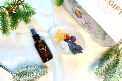 A Soul Gifts subscription box next to a small white bowl holding 4 crystals, a brown spray bottle and fir tree bits.