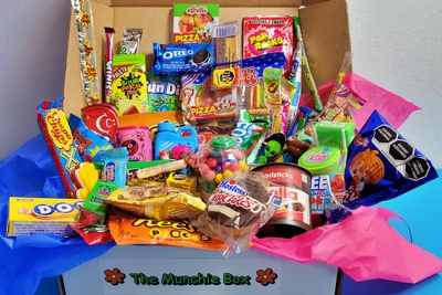 An open The Munchie Box subscription box filled with Reese's Pieces, Oreo's, Dots, Pop Rocks, Sour Patch Kids and more.