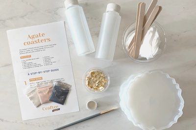The supplies and instruction sheet to make agate coasters with a packets of powder, stirring sticks, gold foil and molds.