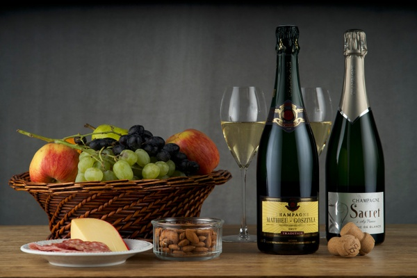 Items from Club Cuvée - Champagne Club subscription box including 2 bottles of champagne, a basket of fruit, and almonds.