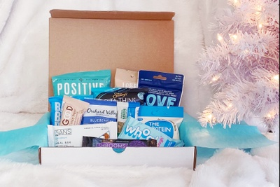 An open, white subscription box filled with healthy snacks. There's a white Christmas tree in the background.