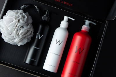 An open, black Men's Shower Experience subscription box containing shampoo, conditioner and body wash.