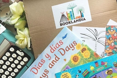 A book subscription box with a Booklandia logo, a few books and a typewriter.