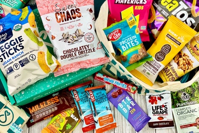 Snacks on and around a SnackSack subscription box. Snacks include veggie sticks, protein bites, nuts, chips and chocolate.