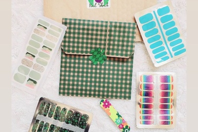 Items from a Nail Shack subscription box including shamrock, blue and rainbow nail stick ons.