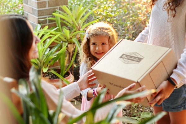 A woman handing a subscription box to another woman while a little girl looks on.