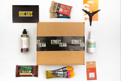 A closed Street Team subscription box for cyclists, with contents around it including a acorn bar, a degreaser, skin repair.