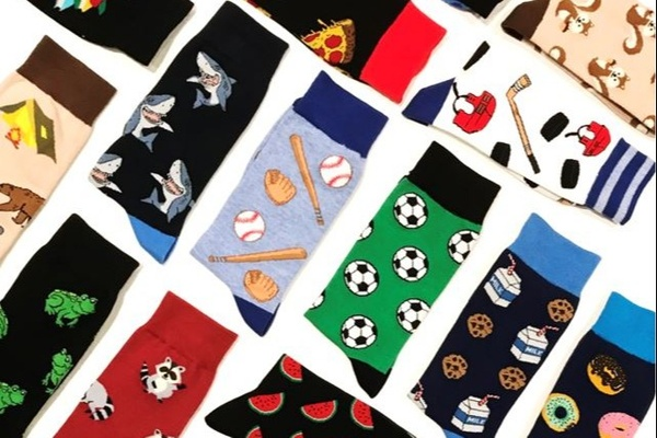 Many socks from the Say it with a Sock subscription box, laid out neatly. There are shark, baseball, soccer and frog socks.