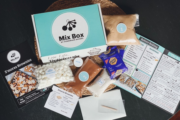 A Mix Box surrounded by various baking mixes, a bag of marshmallows and a few recipe cards.