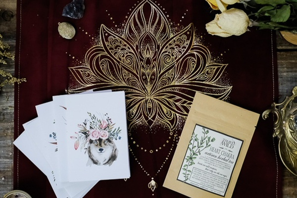 A Heart Chakra subscription box lays on a maroon table runner with an ornate design and cards with a wolf wearing flowers.
