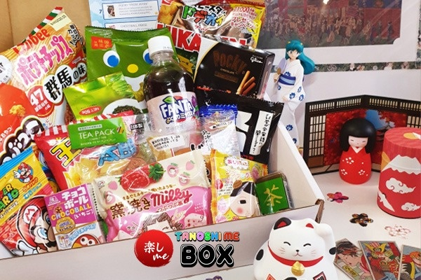 A food subscription box foverflowing with Japanese snacks. There are also various Japanese figures.