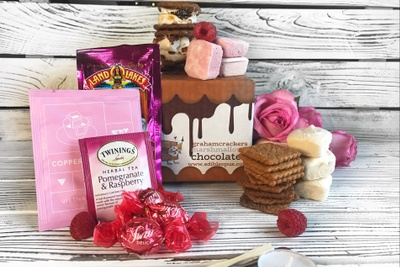 Items from a Marshmallow of the Month Club, including pink and white marshmallows, graham crackers, tea and candies.