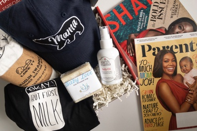 A pregnancy subscription box filled with a cap that says Mama, swaddle blanket, belly oil, soap and a T-shirt.