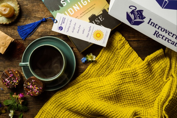 An Introverts Retreat subscription box with a mug of coffee, a book and bookmark, a candle and a flower.