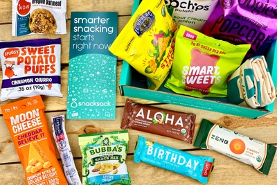 Sweet potato puffs, moon cheese, smart sweets, popcorn and other snacks that come in the Snack Sack subscription box.