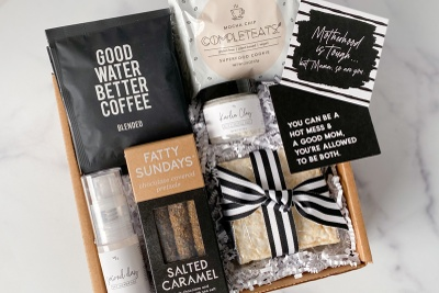 A Mother Snacker subscription box showing a coffee pack, a lactation cookie, chocolate pretzels, and encouraging cards.