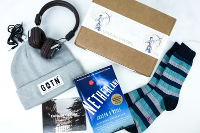 A subscription box labeled Culture Carton surrounded by headphones, a knit hat, striped socks, and a book titled Netherland.