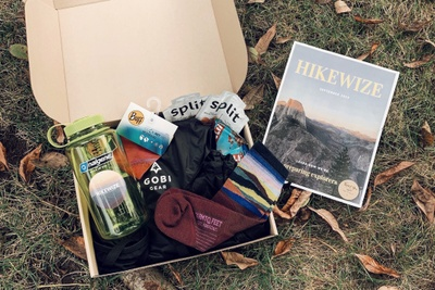 An open Hikewize subscription box on the ground containing a waterbottle, socks, a Clif bar and a Hikewize guide.