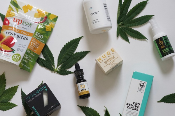 Items from a Cure Crate subscription box, including CBD fruit bites, revive drops, face mask and more.