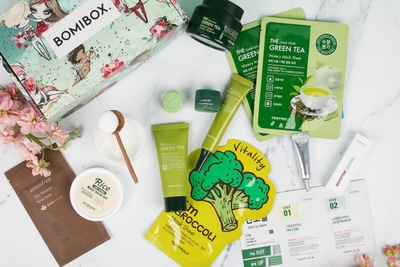 A BomiBox subscription box and items including green tea, and Korean beauty products.