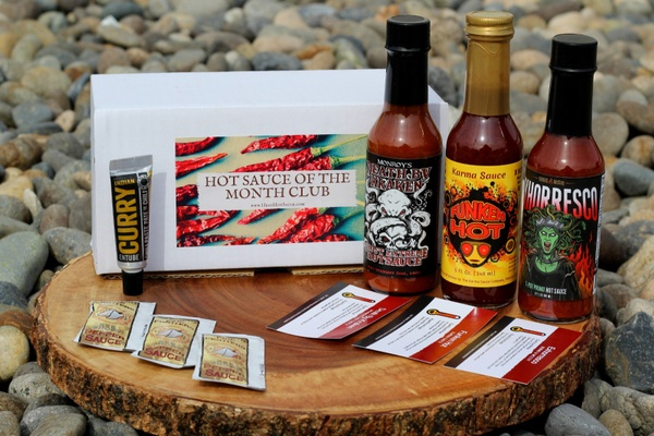 A subscription box that says Hot Sauce of the Month Club, which contains 3 types of hot sauce and a curry paste.
