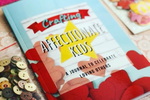 Materials from a Bored to Brilliant subscription box, including buttons and a journal titled Crafting: Affectionate Kids.