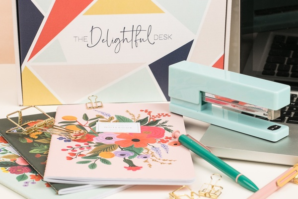 A The Delightful Desk subscription box with a light blue stapler, a green pen, 3 floral journals and gold binder clips.