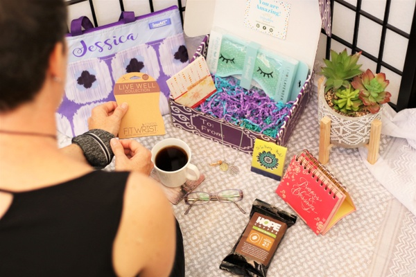 A woman looking at her Fit Wrist, sitting next to a subscription box containing a sleep mask, a protein bar and more.