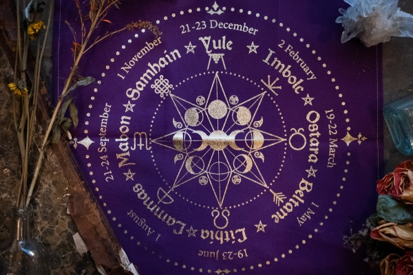 A purple cloth of the Wheel of the Year that has astrological symbols and words on it in silver.
