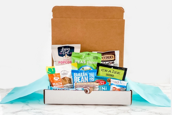 HealthyMe Living Snack Box subscription filled with Bada Bean, Craize seeds, popcorn, dried peas and other healthy snacks.