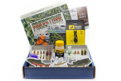 An open Freestone fly fishing subscription box with several types of lures, fish decals, and other supplies for anglers.
