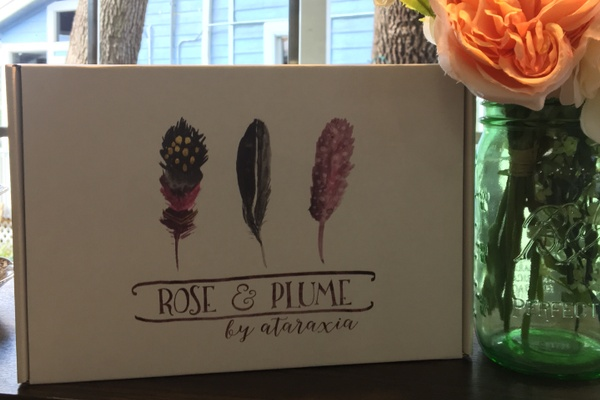 A closed Rose and Plume subscription box next to a mason jar full of pink flowers.