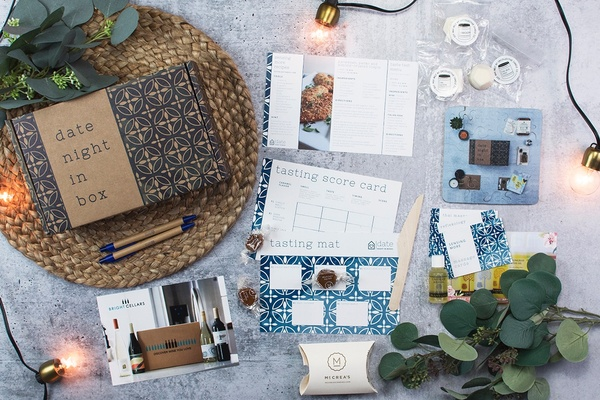 A Date Night in a Box with informational cards, tasting score cards, pens, and tasting mat.