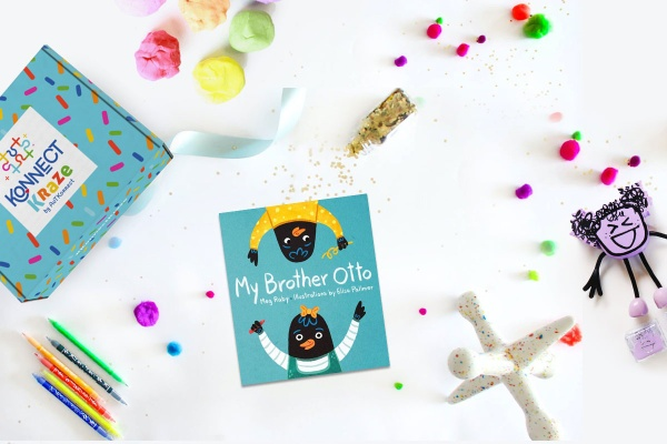 A colorful Konnect Kraze subscription box next to a book titled My Brother Otto, pencils, play dough and other toys.