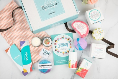 A closed Bath Bevy subscription box surrounded by bath bombs, soaps, bubbles, bunny slippers, candles and more.