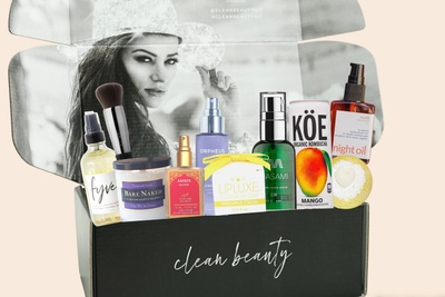 A black box labeled Clean Beauty filled with spray bottles, pump bottles and jars containing clean, sustainable products.