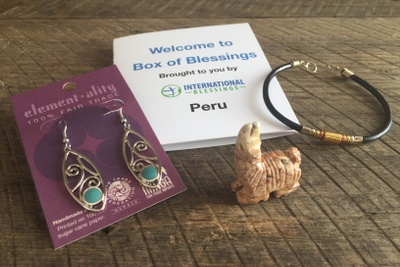 Gold and green dangly ear rings, a carved llama, a choker necklace, and a booklet  called International Blessings.