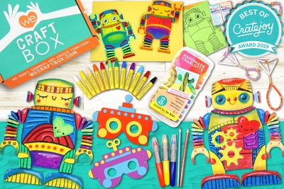 A We Craft subscription box with a few very colorful robots, markers, crayons, colored pencils, and robot masks.