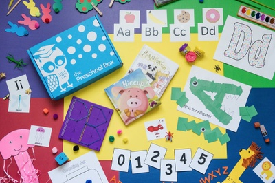Seen from above, a table is covered with arts and crafts, letters and numbers and a blue box that says the preschool box.