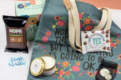 A blue gray tote bag with flowers on it, a candle in a tin, a bag of Hope coffee, and a coin bag.