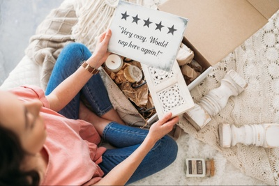 Seen from above, a woman holding a wooden plaque with 5 stars and some words, next to a box full of home décor items.