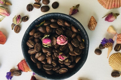 A bowl full of coffee beans with 3 dried roses on top. It is surrounded by seashells, dried flowers and coffee beans.