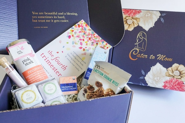 A blue and floral Cater to Mom subscription box next to an open box containing a book, tea, cookies, nipple cream and more.