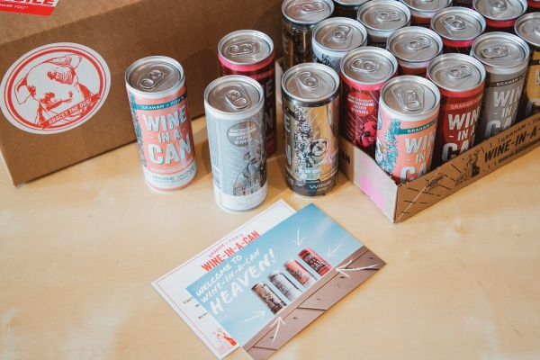 A bunch of cans with the label Wine in a Can and a card that says Welcome to Wine in a can heaven.