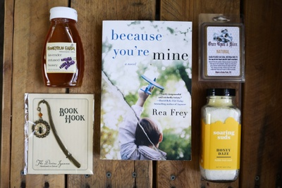 A book titled because you're mine, a jar of honey, a bookmark titled Book Hook, a jar of bath salts called honey daze.