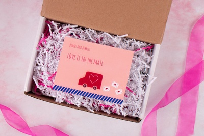 An open Bombs and Bubbles subscription box with a card inside it that says Love is in the mail.