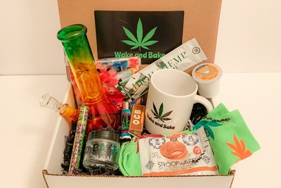 A Wake and Bake subscription box filled with a colorful bong, a Wake and Bake mug, a stroopwafel and other related items.