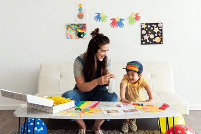 A mom and her son sitting at a table using colorful materials from a Craft and Boogie subscription box.