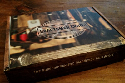 A subscription box labeled Craftsman Crate sitting on a wooden table.