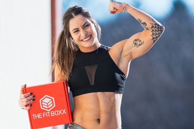 A strong woman flexing her arm and holding an orange subscription box labeled The Fit Boxx.